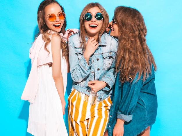 Trzy młode piękne uśmiechnięte dziewczyny w modne letnie ubrania casual. seksowne kobiety dzielą tajemnice, plotki. samodzielnie na niebiesko. zaskoczone emocje twarzy