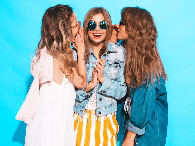 Trzy młode piękne uśmiechnięte dziewczyny w modne letnie ubrania casual. seksowne kobiety dzielą tajemnice, plotki. samodzielnie na niebiesko.
