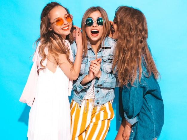 Trzy młode piękne uśmiechnięte dziewczyny w modne letnie ubrania i okrągłe okulary przeciwsłoneczne. seksowne kobiety dzielą tajemnice, plotki. samodzielnie na niebiesko. zaskoczone emocje twarzy