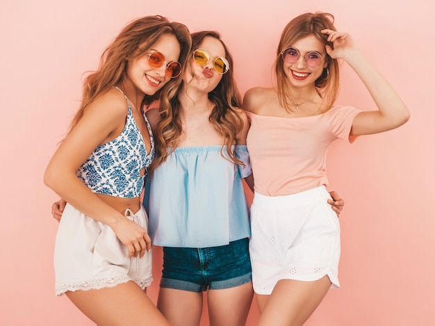Trzy młode piękne uśmiechnięte dziewczyny w modne letnie ubrania. seksowny beztroski kobiet pozować. pozytywne modele zabawy. tulenie