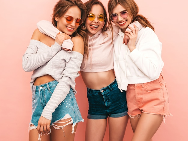 Trzy młode piękne uśmiechnięte dziewczyny w modne letnie ubrania. seksowny beztroski kobiet pozować. pozytywne modele zabawy