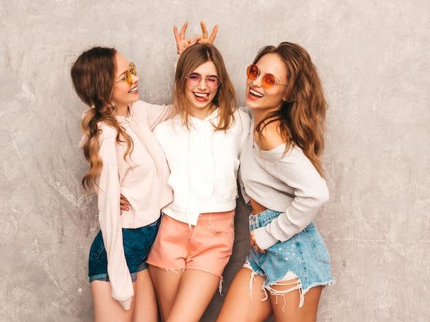 Trzy młode piękne uśmiechnięte dziewczyny w modne letnie ubrania sportowe. seksowny beztroski kobiet pozować. modele w okrągłych okularach przeciwsłonecznych świetnie się bawią. robi rogi palcami na głowie