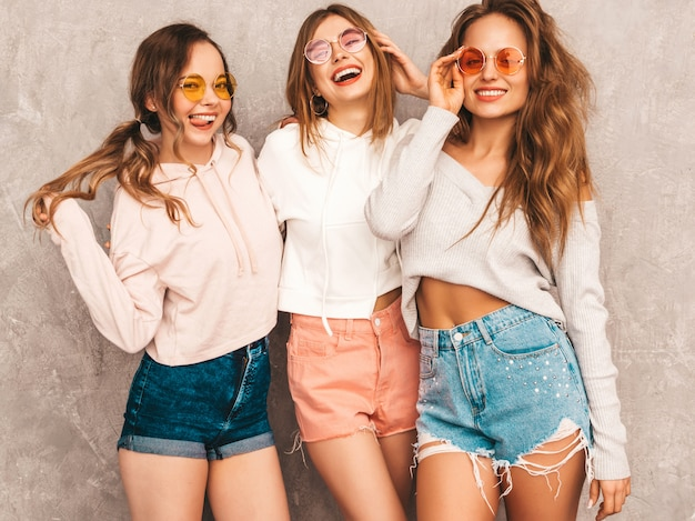 Trzy młode piękne uśmiechnięte dziewczyny w modne letnie ubrania sportowe. seksowny beztroski kobiet pozować. pozytywne modele w okrągłych okularach przeciwsłonecznych świetnie się bawią. tulenie