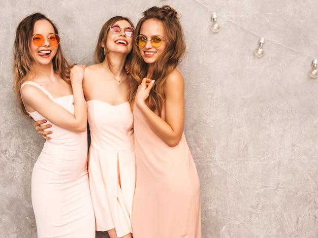 Trzy młode piękne uśmiechnięte dziewczyny w modnych letnich jasnoróżowych sukienkach. seksowny beztroski kobiet pozować. pozytywne modele w okrągłych okularach przeciwsłonecznych świetnie się bawią
