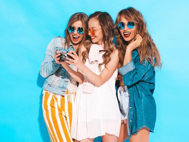 Trzy młode piękne uśmiechnięte dziewczyny w modnych letnich sukienkach i okularach przeciwsłonecznych. seksowny beztroski kobiet pozować. robienie zdjęć aparatem retro