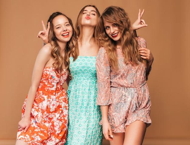 Trzy młode piękne uśmiechnięte dziewczyny w modnych letnich sukienkach i okularach przeciwsłonecznych. seksowny beztroski kobiet pozować.