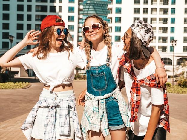 Trzy młode piękne uśmiechnięte hipster dziewczyny w modne letnie ubrania. beztroskie kobiety pozujące na tle ulicy.pozytywne modelki bawią się i szaleją