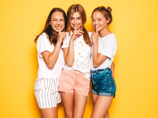 Trzy młode piękne uśmiechnięte hipster dziewczyny w modne letnie ubrania. seksowne beztroskie kobiety pozuje blisko kolor żółty ściany. pozytywne modele pokazujące cisza palec cisza znak, gest