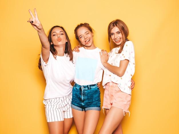 Trzy młode piękne uśmiechnięte hipster dziewczyny w modne letnie ubrania. seksowne beztroskie kobiety pozuje blisko kolor żółty ściany. pozytywne modele wariują i dobrze się bawią. pokazują język