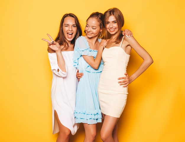 Trzy młode piękne uśmiechnięte hipster dziewczyny w modne letnie ubrania. seksowne beztroskie kobiety pozuje blisko kolor żółty ściany. pozytywne modele wariują i dobrze się bawią. pokazując znak pokoju