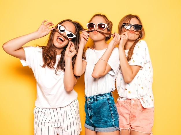 Trzy młode piękne uśmiechnięte hipster dziewczyny w modne letnie ubrania. seksowne beztroskie kobiety pozuje blisko kolor żółty ściany. pozytywne modele wariują i dobrze się bawią, robiąc wąsy z włosami