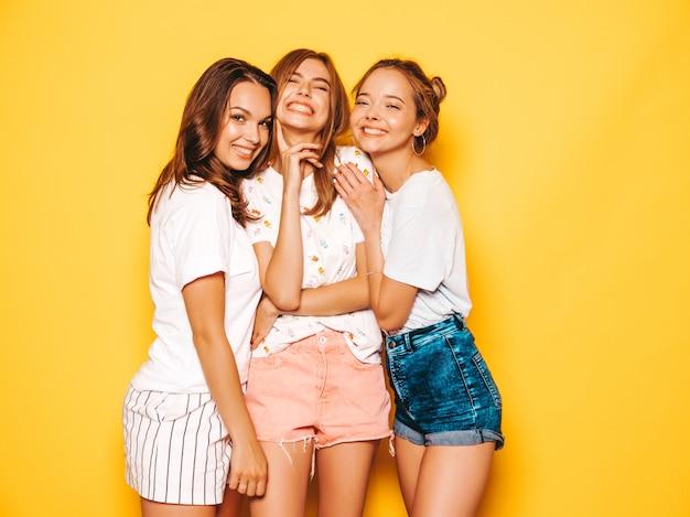 Trzy młode piękne uśmiechnięte hipster dziewczyny w modne letnie ubrania. seksowne beztroskie kobiety pozuje blisko kolor żółty ściany. pozytywne modele wariują i dobrze się bawią