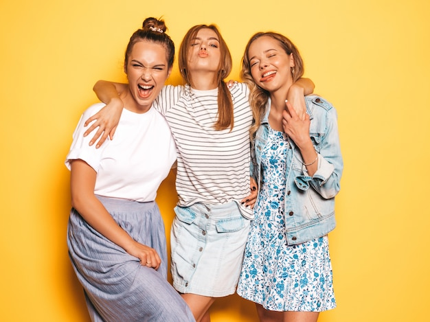 Trzy młode piękne uśmiechnięte hipster dziewczyny w modne letnie ubrania. seksowne beztroskie kobiety pozuje blisko kolor żółty ściany. pozytywne modele zabawy. pokazują język