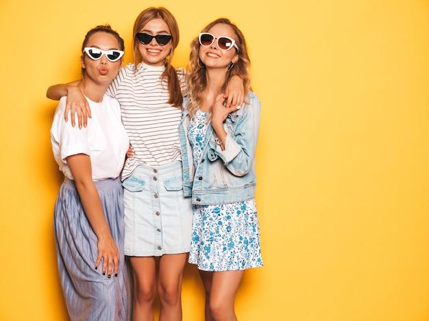 Trzy młode piękne uśmiechnięte hipster dziewczyny w modne letnie ubrania. seksowne beztroskie kobiety pozuje blisko kolor żółty ściany. pozytywne modele zabawy w okularach przeciwsłonecznych