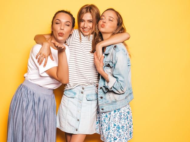 Trzy młode piękne uśmiechnięte hipster dziewczyny w modne letnie ubrania. seksowne beztroskie kobiety pozuje blisko kolor żółty ściany. pozytywne modele zabawy