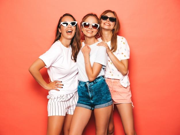 Trzy młode piękne uśmiechnięte hipster dziewczyny w modne letnie ubrania. seksowne beztroskie kobiety pozuje blisko menchii ściany. pozytywne modele wariują i dobrze się bawią. w okularach przeciwsłonecznych