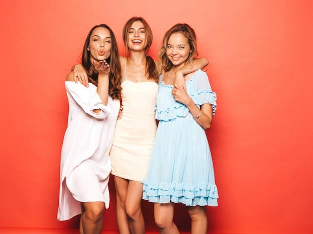 Trzy młode piękne uśmiechnięte hipster dziewczyny w modne letnie ubrania. seksowne beztroskie kobiety pozuje blisko menchii ściany. pozytywne modele wariują i dobrze się bawią