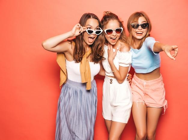 Trzy młode piękne uśmiechnięte hipster dziewczyny w modne letnie ubrania. seksowne beztroskie kobiety pozuje blisko menchii ściany. pozytywne modele zabawy. punktowanie na sprzedaży w sklepie