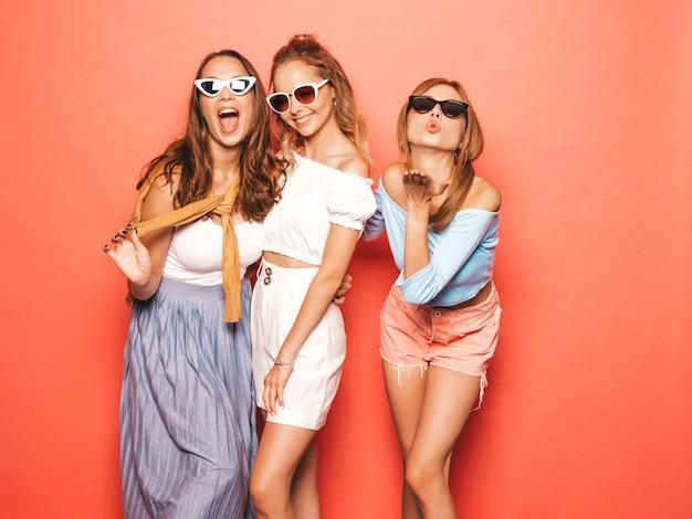Trzy młode piękne uśmiechnięte hipster dziewczyny w modne letnie ubrania. seksowne beztroskie kobiety pozuje blisko menchii ściany. pozytywne modele zabawy. w okularach przeciwsłonecznych