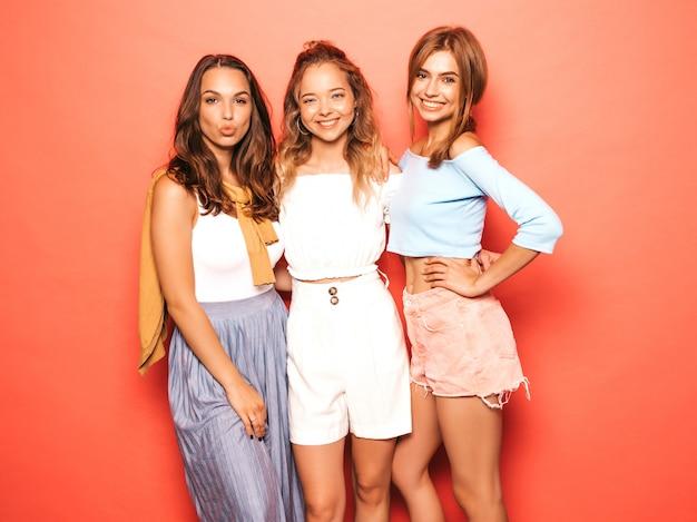 Trzy młode piękne uśmiechnięte hipster dziewczyny w modne letnie ubrania. seksowne beztroskie kobiety pozuje blisko menchii ściany. pozytywne modele zabawy