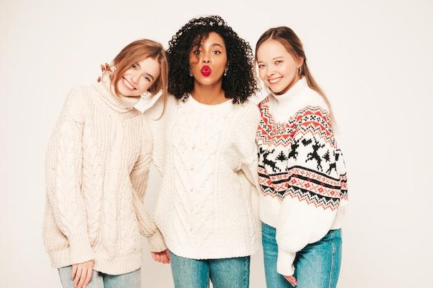 Trzy młode piękne uśmiechnięte hipster dziewczyny w modnych zimowych swetrach. pozytywne modele bawiące się i przytulające