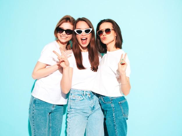 Trzy młode piękne uśmiechnięte kobiety hipster w modnej, tej samej letniej białej koszulce i dżinsach