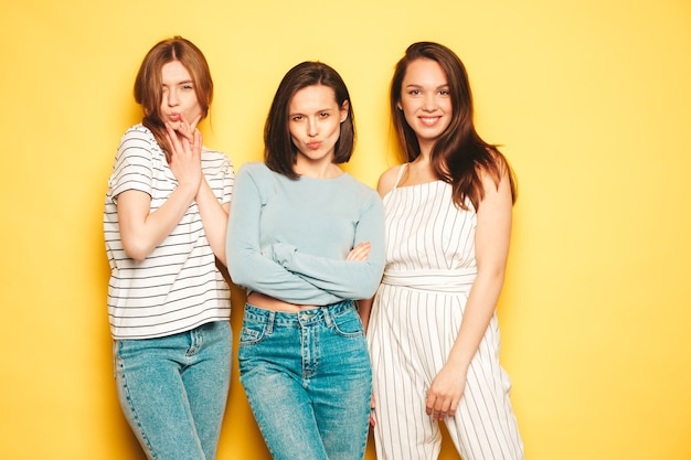 Trzy młode piękne uśmiechnięte kobiety hipster w modnych letnich ubraniach