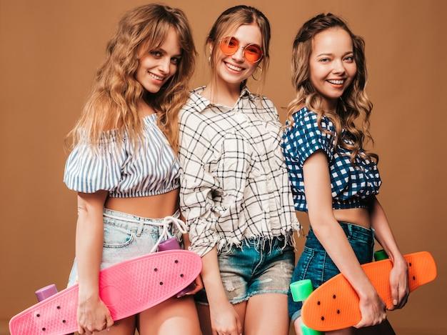 Trzy młode stylowe uśmiechnięte piękne dziewczyny z kolorowymi deskorolkami grosza. kobieta w lecie kraciaste koszule ubrania pozowanie. pozytywne modele zabawy