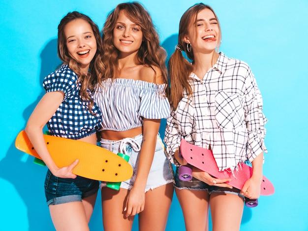 Trzy młode stylowe uśmiechnięte piękne dziewczyny z kolorowymi deskorolkami grosza. kobiety w lecie pozowanie ubrania kraciaste koszule. pozytywne modele zabawy