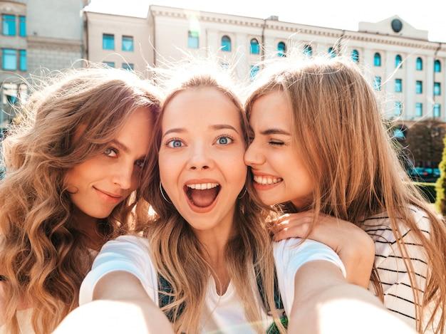 Trzy młode uśmiechnięte kobiety hipster w letnie ubrania. dziewczyny robienia zdjęć autoportretów na smartfonie. modele pozowanie na ulicy. kobieta pokazująca pozytywne emocje na twarzy