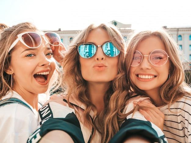 Trzy młode uśmiechnięte kobiety hipster w letnie ubrania. dziewczyny robienia zdjęć autoportretów na smartfonie. modele pozowanie na ulicy. kobieta z pozytywnymi emocjami twarzy w okularach przeciwsłonecznych