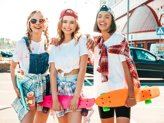 Trzy młode uśmiechnięte piękne dziewczyny z kolorowych deskorolek grosza.