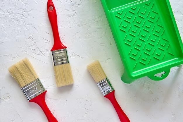 Trzy muśnięcia z czerwonymi rękojeściami i zieloną farby tacą na bielu betonują tło. narzędzia i akcesoria do remontu domu. widok z góry