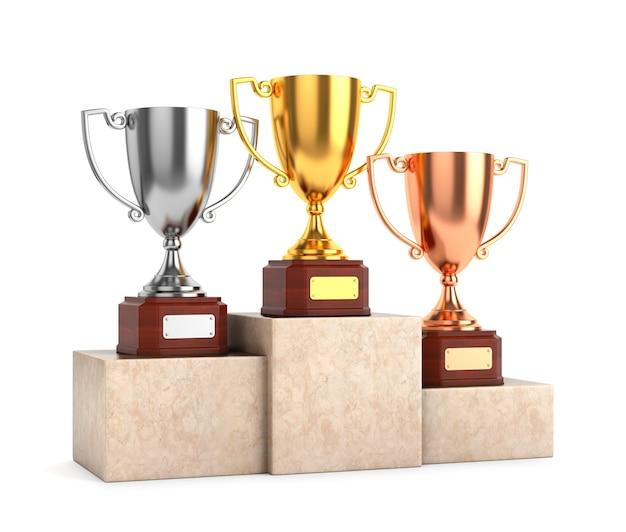 Trzy nagrody pucharowe trofea: złote, srebrne i brązowe puchary na marmurowym cokole na białym tle.