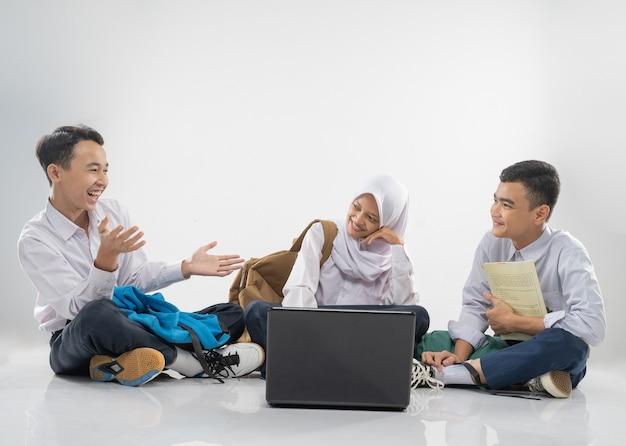 Trzy nastolatki w gimnazjalnych mundurkach siedzą na podłodze i uczą się razem z żartobliwym...