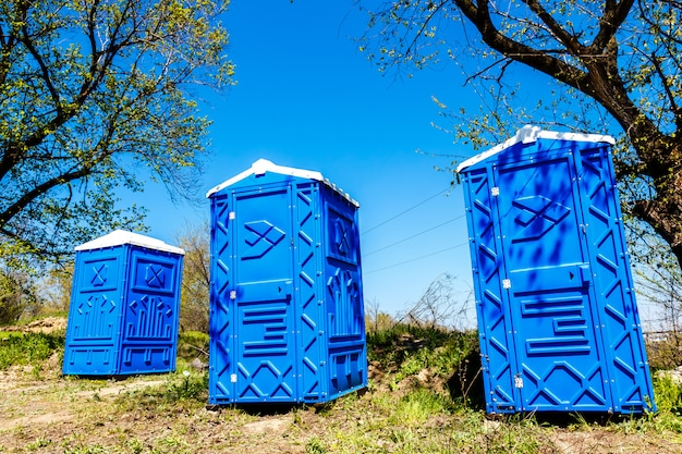 Trzy niebieskie kabiny chemiczne toalety w parku w słoneczny letni dzień.