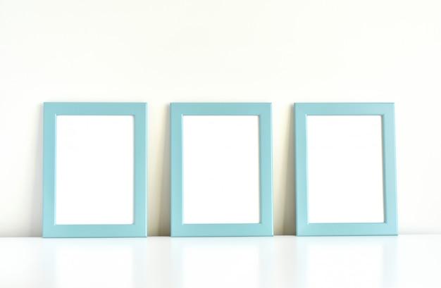 Trzy niebieskie ramki na białym stole.