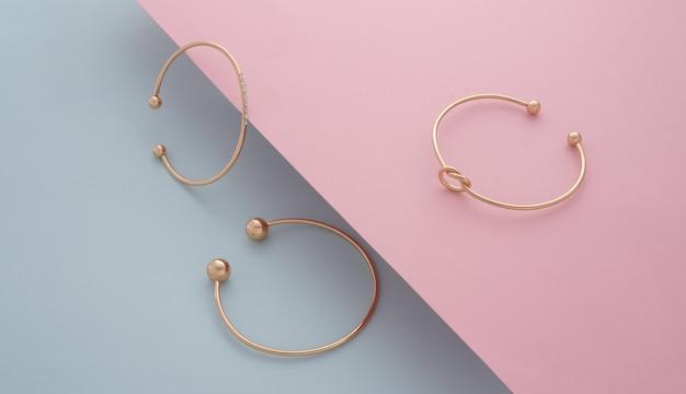 Trzy nowoczesne złote bransoletki na różowym i niebieskim skośnym tle papieru