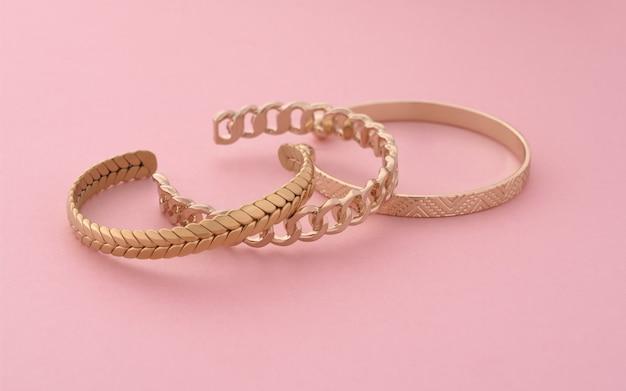 Trzy nowoczesne złote bransoletki ułożone na różowym tle