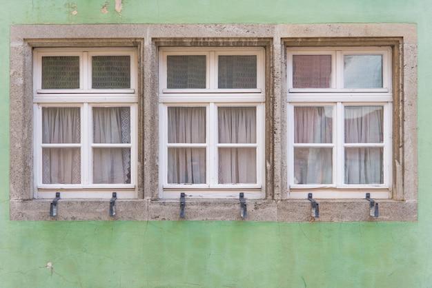 Trzy okna na klasycznej zielonej ścianie w europie