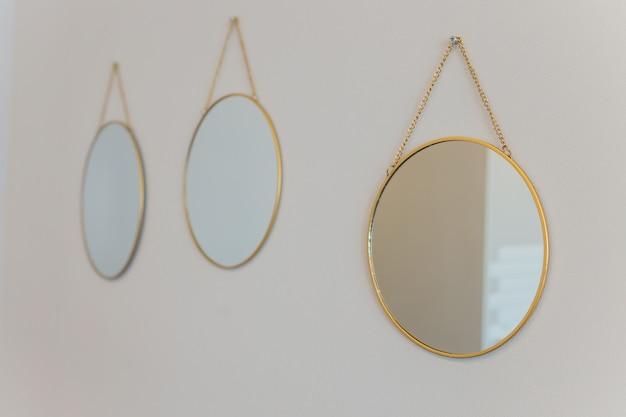 Trzy okrągłe lustro z podświetleniem na tle beżowych ścian.