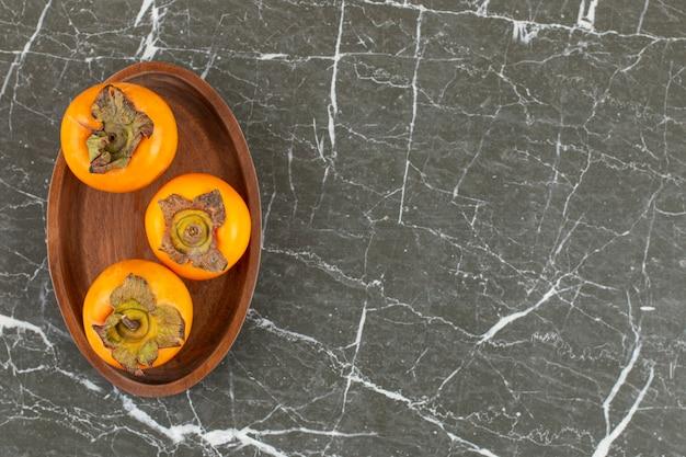 Trzy organiczne persimmon na drewnianym talerzu.