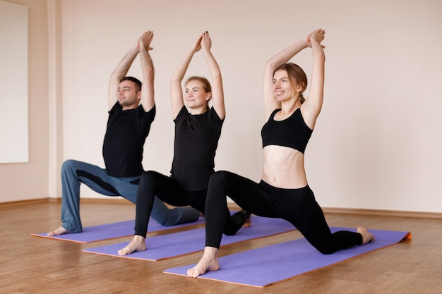 Trzy osoby na zajęciach uprawiają jogę