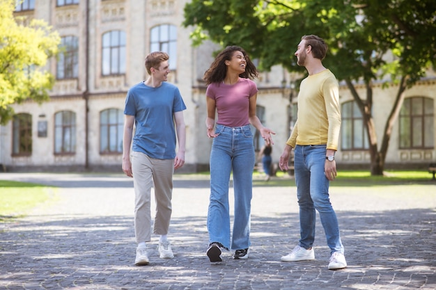 Trzy osoby spacerujące po parku i dyskutujące o czymś