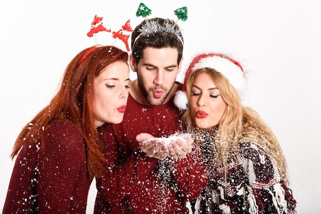 Trzy osoby z santa kapelusz rozdmuchu płatki śniegu z rąk