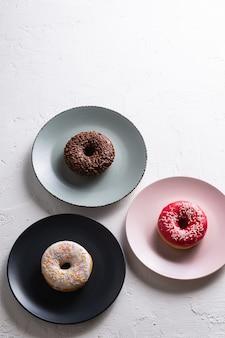 Trzy pączki na talerzach, czekoladowy, różowy i waniliowy pączek z posypką, słodki glazurowany deser na białym betonowym stole z teksturą, widok pod kątem
