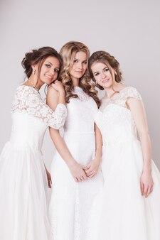 Trzy panny młode stanowią w studio na szaro