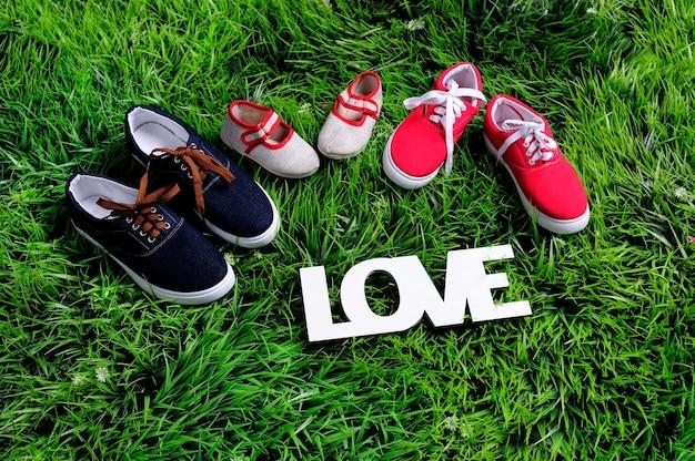 Trzy pary butów reprezentujących koncepcję rodziny, rozwoju, edukacji i wspólnoty