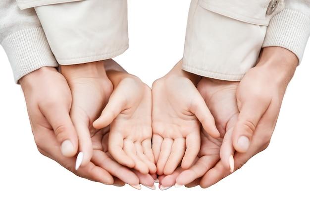 Trzy pary rąk rodzina ojciec matka i dziecko izolują na białym tle