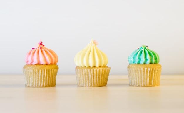 Trzy pastelowego koloru filiżanki tort target639_0_ na biel stole.